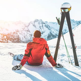 skier sitting in the snow with their skis stood up. Overloking a beautiful mountain scape