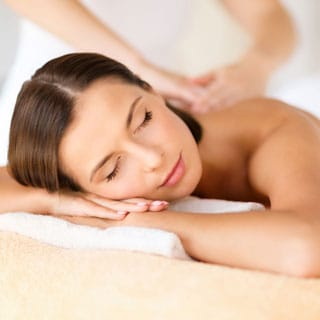 woman looking contented and relaxed whilst receiving a massage